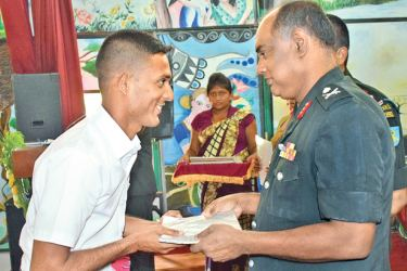 A beneficiary receives a certificate from Commissioner General of Rehabilitation Major General Janaka Ratnayake.