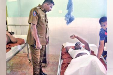 One of the injured students speaks to a policeman at the Hemmathagama hospital.
