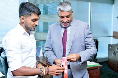 Mithun showing one of his medals to the SriLankan Airlines CEO Capt. Suren Ratwatte at his office.
