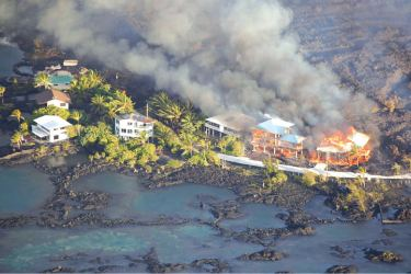 Lava destroys homes in the Kapoho area, east of Pahoa, during ongoing eruptions of Hawaii's Kilauea volcano.
