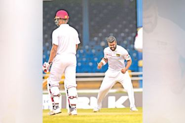 Lahiru Kumara (R) of Sri Lanka celebrates the dismissal of Kieran Powell (L) of West Indies during day one of the 1st Test at Queen's Park Oval, Port of Spain, Trinidad, on Wednesday. – AFP