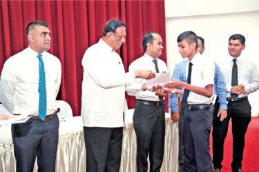 Minister  John Amaratunga presents the first scholarship to a student from Koggala flanked (on left) by Director General, SLITHM Buddhika Hewawasam