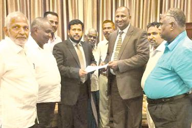 Minister  Rishad Bathiudeen handing over the appointment letter to S.M.M. Ismail.