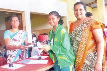 Iresha Sandarenu Fernando receives the Athletic Champion's Certificate and the cup from a Senior Sports Instructor in the presence of her coach/sports teacher Harshani Manorika Saputhanthri, at the Panadura Sports Ground, after the Kalutara Zonal Athletic meet, held recently.  Picture by Kalutara Central Special Corr. H. L. Sunil Shantha