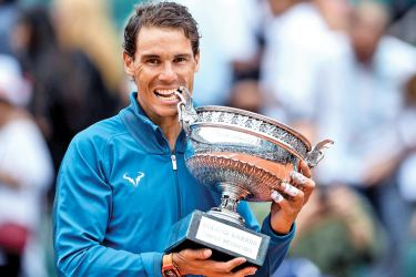 Spain's Rafael Nadal poses with the Mousquetaires Cup (The Musketeers) after his victory in the men's singles final match against Austria's Dominic Thiem, on day fifteen of The Roland Garros 2018 French Open tennis tournament in Paris on June 10. AFP