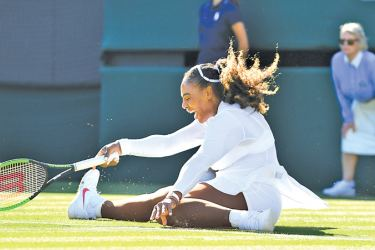 US player Serena Williams slips on the grass as she tries to return against Netherlands' Arantxa Rus during their women's singles first round match on the first day of the 2018 Wimbledon Championships at the All England Lawn Tennis Club in Wimbledon on Monday.  – AFP