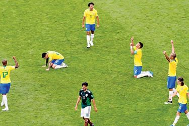 Mexico's Carlos Vela looks dejected as Brazil's Thiago Silva, Marquinhos and team mates celebrate victory after the match.