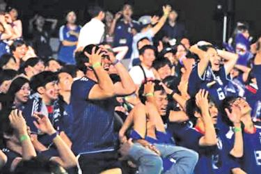 Supporters of Japan soccer team react as they watch a live broadcasting of the World Cup soccer match between Japan and Belgium at a public viewing venue.