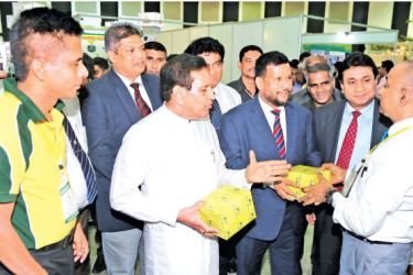 Minister of Health, Nutrition and Indigenous Medicine, Rajitha Senaratne, Minister of Industry and Commerce, Rishad Bathiudeen and President of National Chamber of Commerce, Sujeewa Samaraweera discuss with a Sri Lankan traditional medicine exhibitor in Colombo