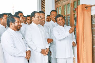 Higher Education and Cultural Affairs Minister Wijeyadasa Rajapakshe unveiling the plaque in the presence of President Maithripala Sirisena, marking the opening of the new two - storey Bhikku hostel, built at Rs. 14.3 million at Lankapura Pulasthigama Siriparakum Pirivena in Polonnaruwa.