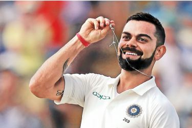 India's captain Virat Kohli holds his wedding ring as he celebrates scoring his century on the second day of the first Test cricket match between England and India at Edgbaston in Birmingham, central England on August 2. AFP
