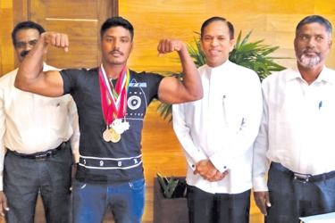 Abdul Ali Mohamed Asath shows his medals in the presence of State Minister of Highways and Road Development Dr. M.L.A.M.Hisbullah.