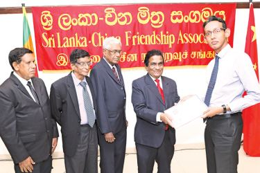 SLCFA President and Attorney-at-Law Ananda Goonatilleke presenting an award to Professor Sandagomi Coperahewa, while others look on.