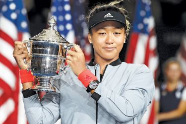 Naomi Osaka of Japan poses with the championship trophy after winning the Women's Singles finals match against Serena Williams of the United States at the US Open at USTA Billie Jean King National Tennis Center on Saturday. – AFP