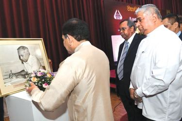 Health Minister Dr. Rajitha Senaratne pays floral tribute to the late Prof. Senaka Bibile.  Health Deputy Minister Fizal Kassim and others look on.