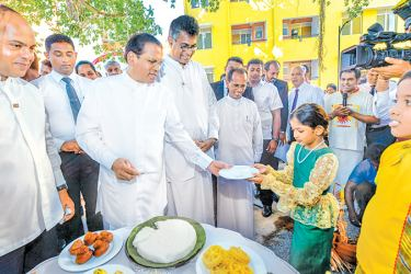 "President Maithripala Sirisena, the Chief Guest at the opening of the ""Lake Crest Residencies"" housing complex with 500 apartment units at Mulleriyawa, Mandawila, handing over a plate of 'Kiribath'(Milk Rice) to a child from one of the house recipient families at the opening ceremony.Minister Patali Champika Ranawaka and MP S.M. Marikkar look on. Picture by Sudath Silva"