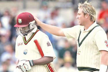 Shane Warne gives a pat on the head to Brian Lara.