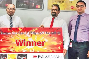 Pan Asia Bank Senior Manager Cards Centre Malintha Liyanage with the winner for the month of June S.T.M.S.P. Perera and Assistant Manager Cards Centre Pan Asia Bank Sanjaya Gajanayake.