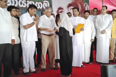 Prime Minister Ranil Wickremesinghe presents a title deed to a woman at the ceremony. Ministers Sajith Premadasa and Gayantha Karunathilaka and others look on.