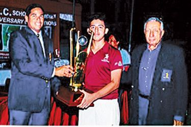 captain of Sobers house Mutahhar Nasir receiving the overall winners trophy from chief guest Malintha Warnapura director of CCC School of cricket Nelson Mendis looks on.