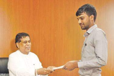 Transport and Civil Aviation Minister Nimal Siripala De Silva presenting a letter of commendation to Janith Dimantha Withaanarachchi.