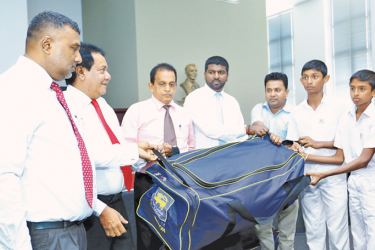 Sports Ministry officials hand over cricket gear to a school cricket team members