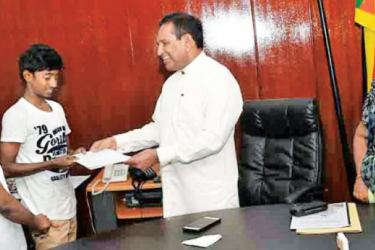 Health Minister Dr. Rajitha Senaratne presents a cheque from the Health Development Fund to one of the youth.