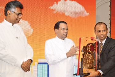 Chairman UDA, Dr. Jagath Munasinghe presents a token to President Maithripala Sirisena who was the Chief Guest at the UDA 40th anniversary celebrations held at Kingsbury Colombo on Tuesday. Megapolis and Western Development Minister Patali Champika Ranawaka looks on. Picture by Sudath Malaweera