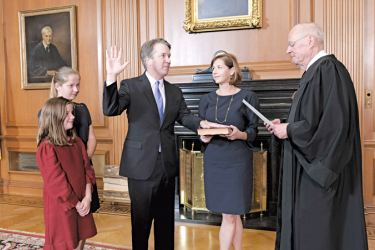 Justice Anthony M. Kennedy, (Retired) administers the Judicial Oath to Judge Brett M. Kavanaugh in the Justices' Conference Room, Supreme Court Building on Saturday in Washington, DC. Mrs. Ashley Kavanaugh holds the Bible while Kavanaugh's two daughters look on. - AFP