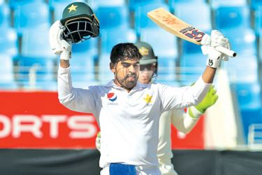 Pakistan cricketer Haris Sohall (L) gestures as he celebrates his century (100 runs) during day two of the first Test match in the series between Australia and Pakistan at Dubai International Stadium in Dubai on October 8. AFP