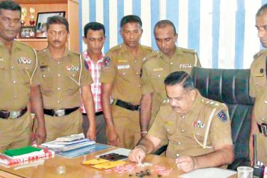 Galle police officers inspect seized heroin.