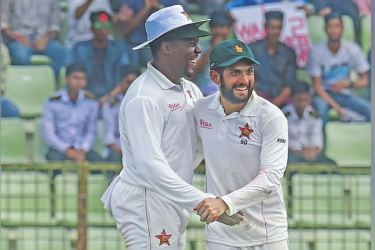 Zimbabwe cricket captain Hamilton Masakadza (L) and Sikandar Raza (R) celebrate after the dismissal of the Bangladesh cricketer Nazmul Hossain Shanto during the fourth day of the first Test cricket match between Bangladesh and Zimbabwe in Sylhet on November 6. AFP