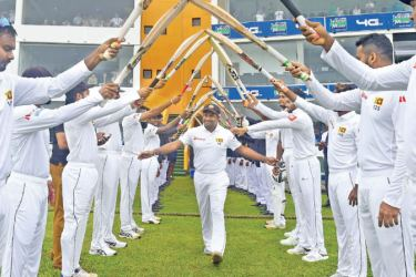 Sri Lanka cricketer Rangana Herath is given a guard of honour as he takes the field on his final Test appearance on the first day of the first cricket Test against England at Galle International Stadium yesterday. - AFP