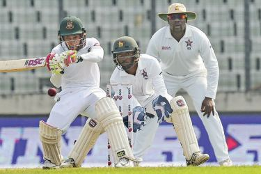 Bangladesh cricketer Mushfiqur Rahim (L) plays a shot as the Zimbabwe cricketer Regis Chakabva (C) and captain Hamilton Masakadza (R) look on during the second day of the second Test cricket match between Bangladesh and Zimbabwe at the Sher-e-Bangla National Cricket Stadium in Dhaka on November 12. AFP