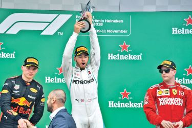 Lewis Hamilton (C) celebrates with his trophy after winning the F1 Brazil Grand Prix, while a rueful Max Verstappen (L) who finished second for Red Bull looks on. AFP