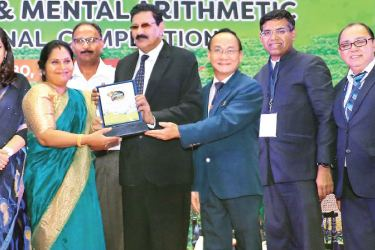 Head of the Champion Center, Shanthi Sithamparam receiving award from Hassim Omar. Picture by Ruzaik Farook