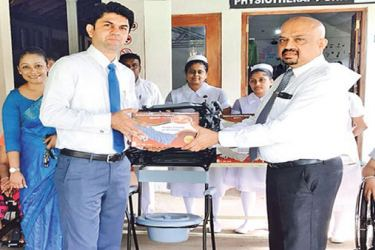 Pan Asia bank Area Manager Central, Yohan Ebell habnds over the hospital equipments to Dr Chaminda Ekanayake.