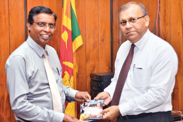 Chairman of Lake House Wasanthapriya Ramanayake hands over the first winning coupon to General Manager Abhaya Amaradasa