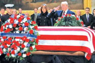 US President Donald Trump and First Lady Melania Trump pay their respects as US President George H. W. Bush lies in state in the Rotunda of the US Capitol in Washington, DC on Monday. - AFP