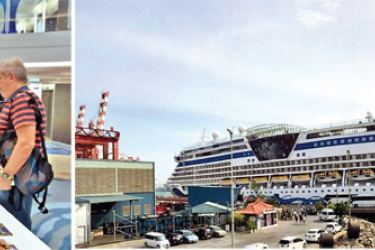 Visitors being briefed by a Tourist Information Centre (TIC) official on the cruise (right) the AIDAbella cruise ship