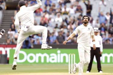 India's Ishant Sharma (R) celebrates with captain Virat Kohli (L) after taking the final Australian wicket on the final day of the third cricket Test match at Melbourne on Sunday. India won by 127 runs to take a 2-1 lead in the four-match series. - AFP