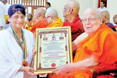 Most Ven. Abewela Pagnnasara Thera handing the the certificate to Dr. Consy Perera. Picture by Saman Sri Wedage.