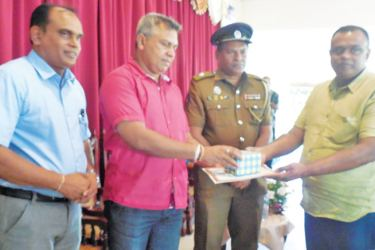 Panadura Police Public Relations Officer Aruna Shantha being awarded by Panadura Police Division SSP Laksiri Wijesena. Picture by Vineetha Manel Gamage, Halthota Group Corr.