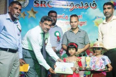 Eastern Province Pre-school Education Bureau Chairman M.A. Ameerdeen handing a gift to a child while others look on. Picture by I.L.M. Rizan, Addalaichenai Central Corr.