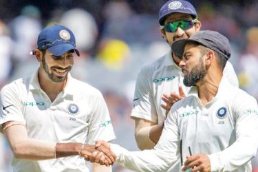 Jasprit Bumrah (left) is congratulated by his captain Virat Kohli after bowling India to victory over Australia in the third Test at Melbourne.
