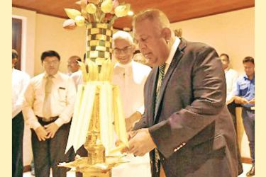 Minister Mangala Samaraweera, lighting the traditional oil lamp looked on by State Minister Eran Wickramaratne and officials at the Ministry yesterday.
