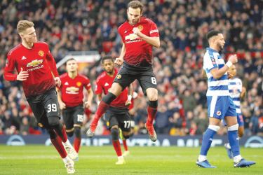 Manchester United's Juan Mata celebrates scoring their first goal in their FA Cup Third Round match against Reading at Old Trafford on Saturday. – AFP