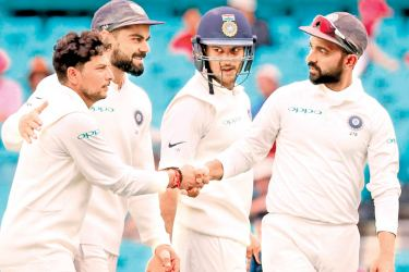 India's Kuldeep Yadav (L) is congratulated by captain Virat Kohli (2nd L) and teammates as they walk off the ground after taking five wickets during the fourth day's play of the fourth and final cricket Test between India and Australia at the Sydney Cricket Ground on Sunday. AFP