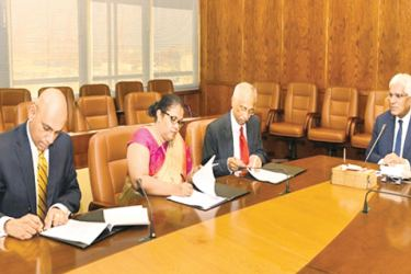 Dr. Indrajit Coomaraswamy, Governor of CBSL, representatives of the three regulators, H. A. Karunaratne, Deputy Governor of CBSL, Vajira Wijegunawardane, Director General of SEC and Damayanthi Fernando, Director General of IRCSL signing the MoU
