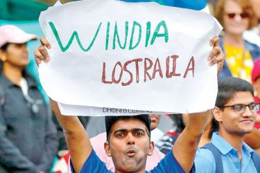 An Indian cricket team supporter holds up a sign as he celebrates after India won the Test series against Australia at the Sydney Cricket Ground on Monday. - AFP